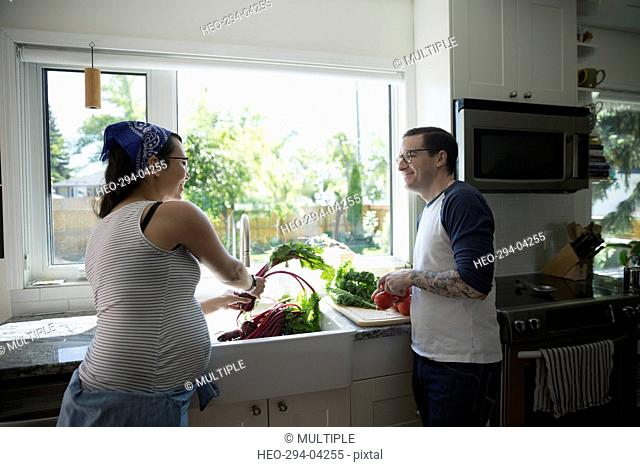 Pregnant couple washing vegetables at kitchen sink