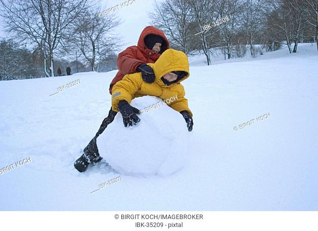 Two boys rolling big snowball