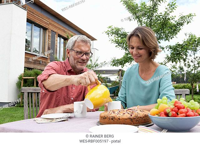 Mature couple in garden having afternoon break