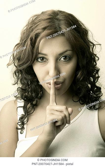 Portrait of a young woman making a silence gesture