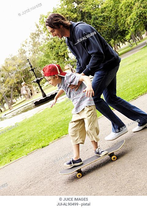 Father helping son skateboard