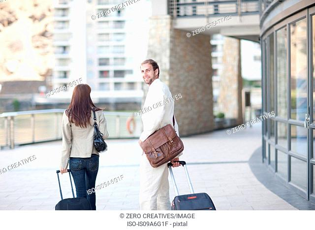 Young man and young woman with suitcases