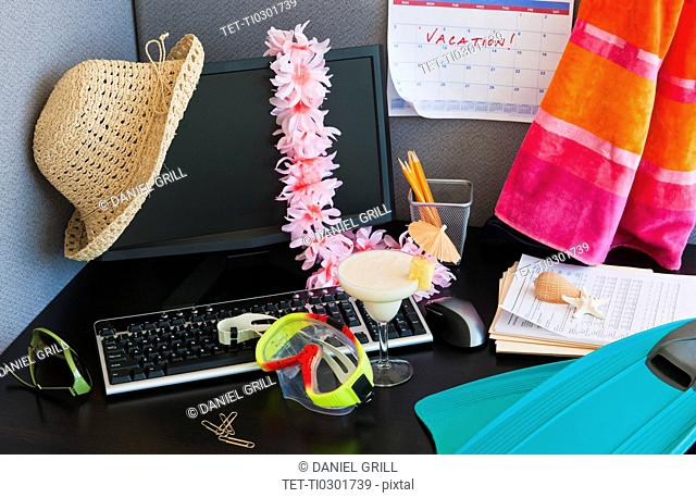 Close up of office desk with vacation equipment