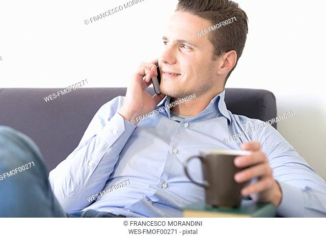 Smiling businessman on couch with smartphone and cup of coffee