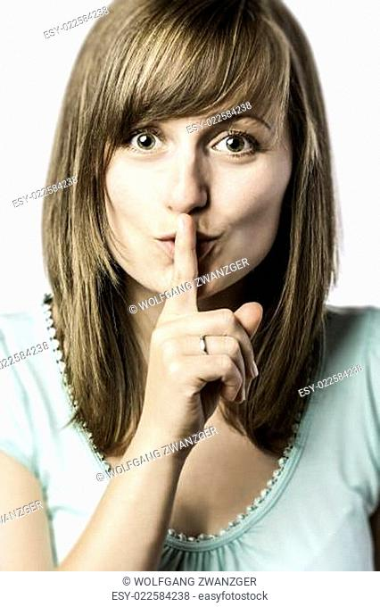 Young woman holds a finger to her mouth
