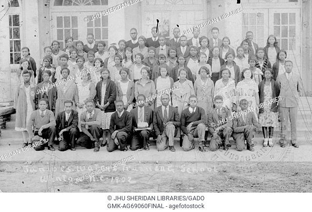 Full length portrait of a co-ed class of African-American students with two teachers, all students wearing uniforms; Winton, North Carolina, 1920