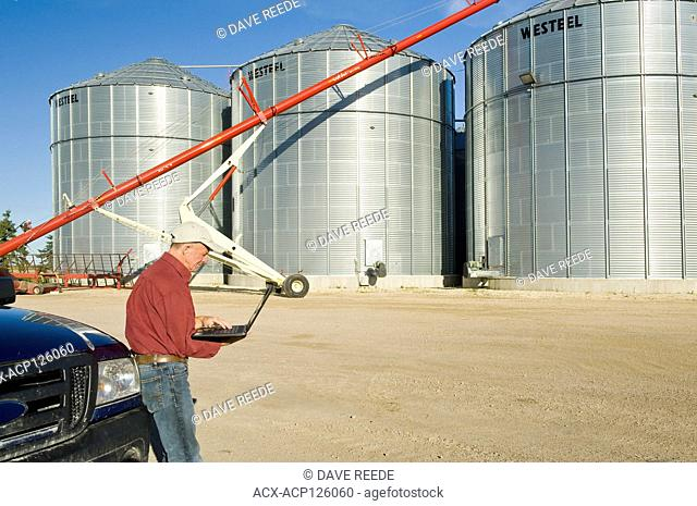 man using a computer next grain bins in a farmyard, near Lorette, Manitoba
