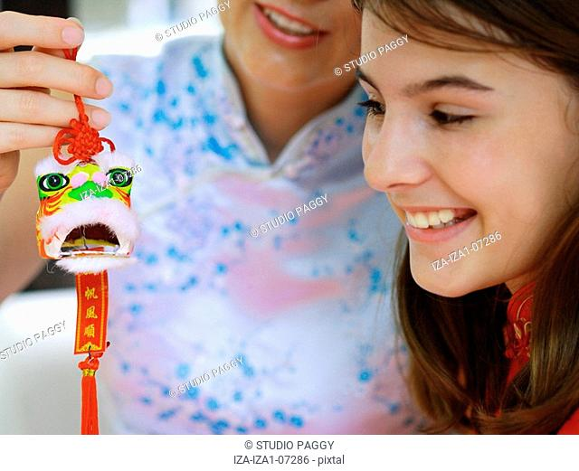 Close-up of a teenage girl with her mother holding a good luck charm
