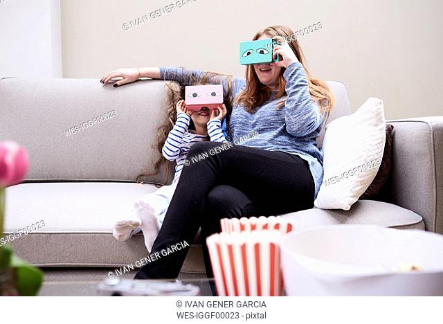 Mother and little daughter sitting on the couch having fun with Virtual Reality Glasses