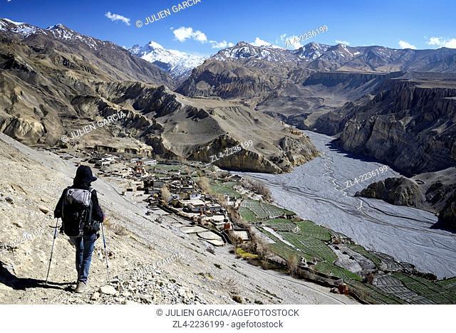 Trekker going down towards the village of Tangge. Nepal, Gandaki, Upper Mustang (near the border with Tibet). Model Released