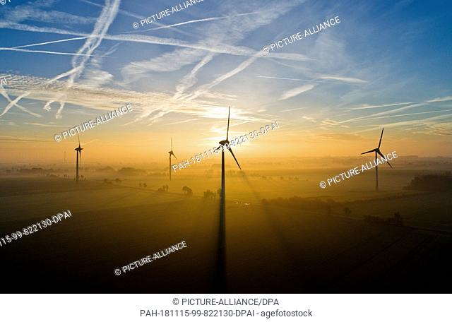 15 November 2018, Lower Saxony, Sehnde: The sun rises behind windmills and bathes the morning fog in golden light. (aerial view with drone) Photo: Julian...