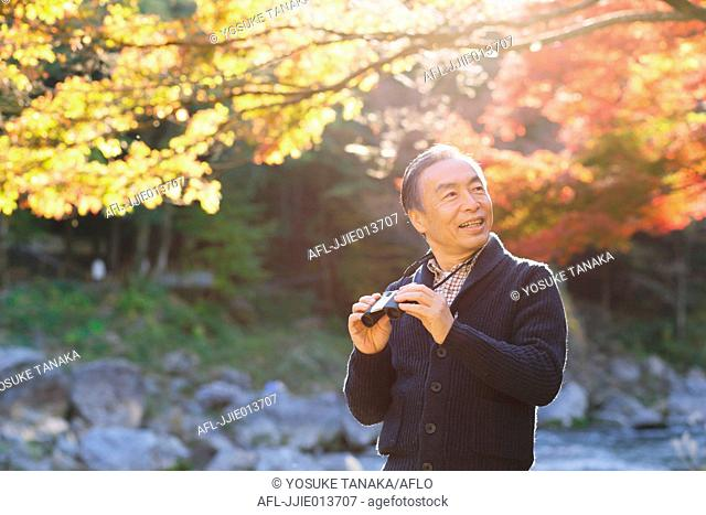 Senior Japanese man with binoculars in a traditional park in Autumn
