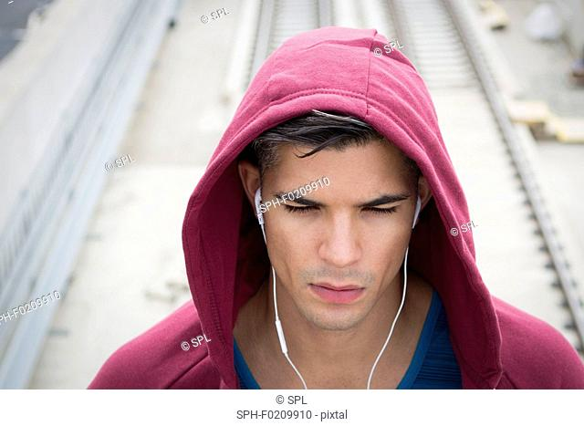Young man wearing ear phones and hooded top