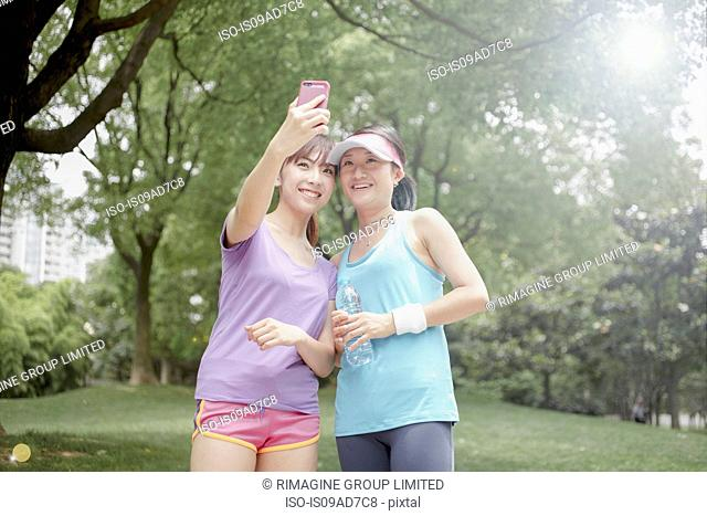Female friends taking picture of themselves in park