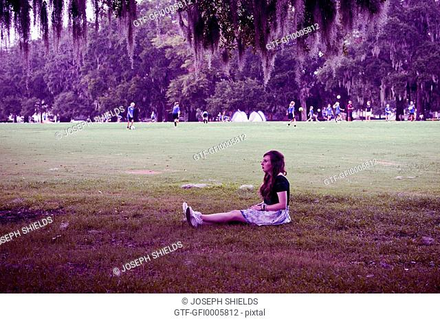 Young woman, 19 years old, sitting alone on playing field