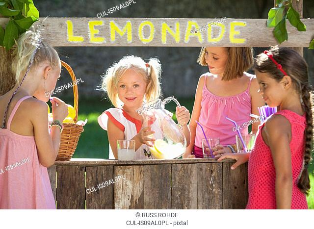 Candid portrait of four girls at lemonade stand in park