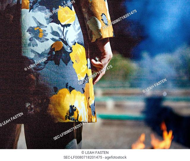 Back view of woman standing by bonfire