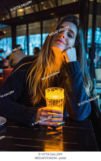 Paris, France, portrait of smiling young woman with glass of beer in a pub in the evening