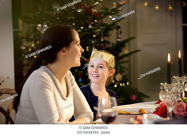 Happy mother and daughter in paper crown at candlelight Christmas dinner table