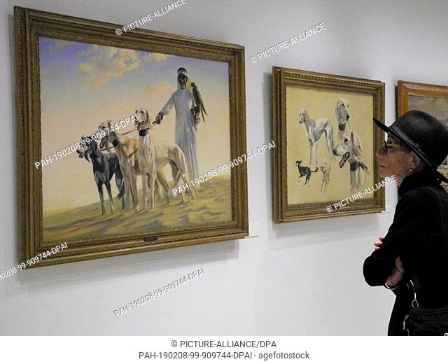 """08 February 2019, US, New York: A visitor stands in front of the paintings """"""""The Falconer"""""""" (l) and """"""""Studies of Salukis"""""""" (r) by artist Donald Grant in the..."""