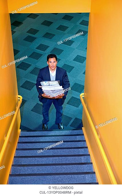 Office worker carrying stack of papers