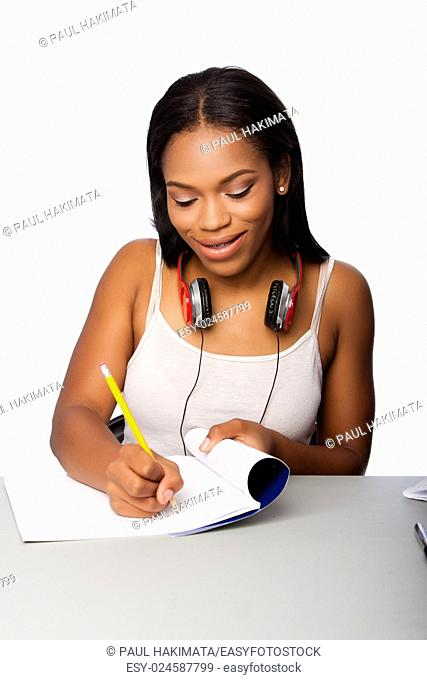 Cute beautiful happy smiling teenage student doing homework writing in notebook sitting at desk, on white