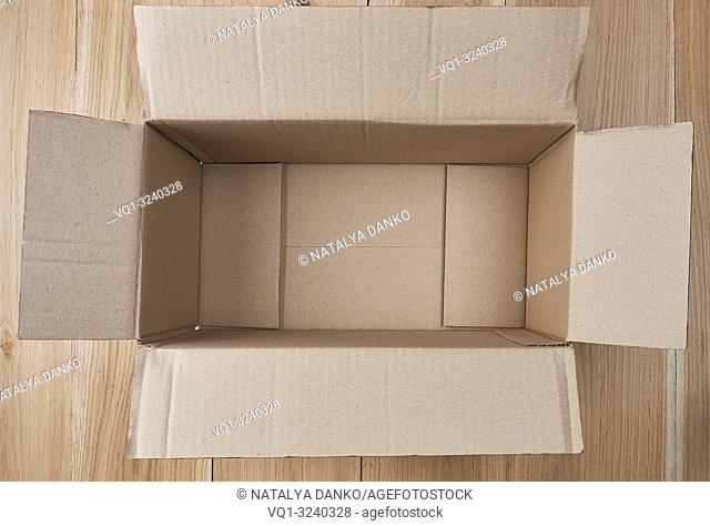 open empty rectangular box of brown cardboard on a wooden background, top view