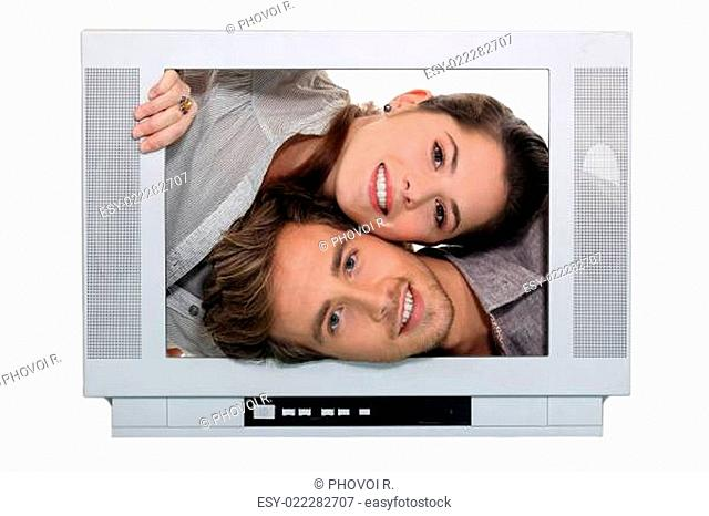 Young people passing heads through TV screen