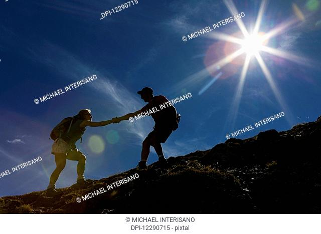 Silhouette of male hiker helping female hiker up a rocky slope with blue sky and sun burst; Waterton, Alberta, Canada