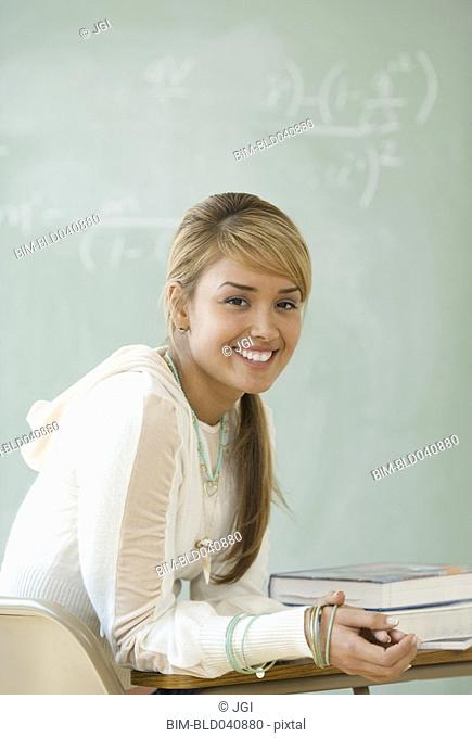 Young Hispanic woman sitting at school desk