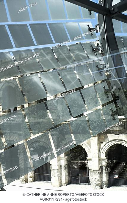 Glass and stainless steel light deflectors flutter like bunting on the facade of the Roman Museum at Nimes to reveal the massive stone arches of the Roman Arena