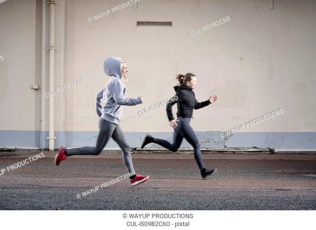 Two female runner friends running on urban road