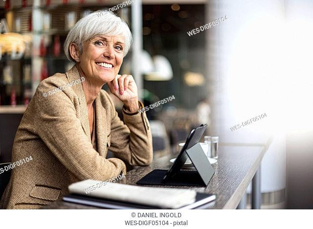 Portrait of smiling senior businesswoman with tablet in a cafe