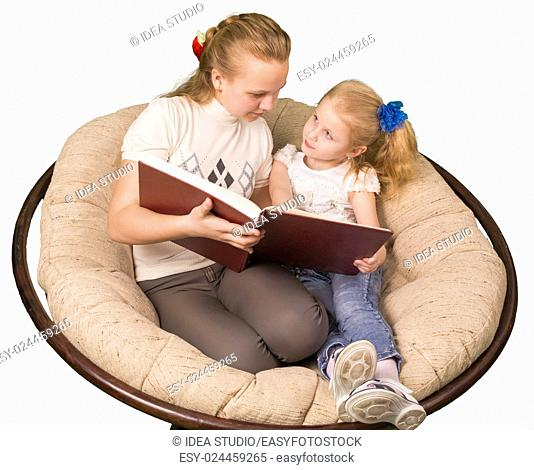 Two sisters reading book isolated on white backhround