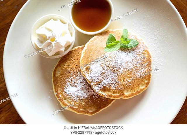 Two pancakes with maple syrup and whipped cream