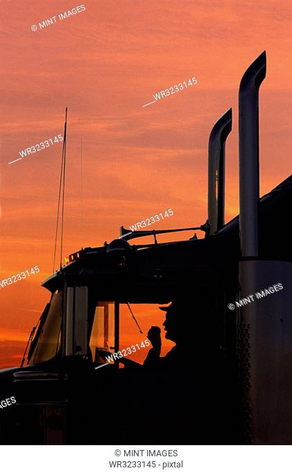 A silhouette of a truck driver on his CB radio in the cab of his Class 8 truck tractor