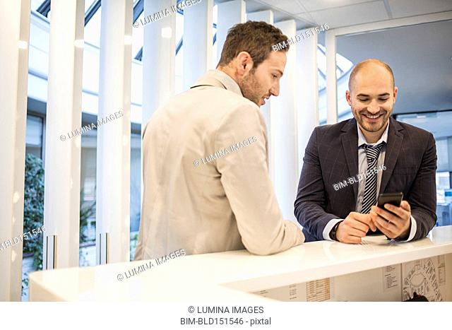 Caucasian businessmen using cell phone in office lobby