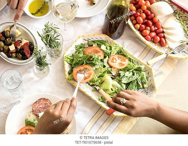 Hands serving salad