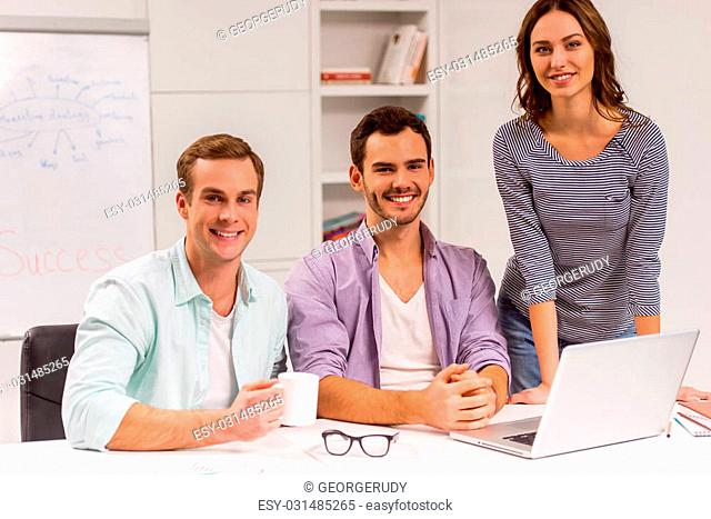Two young attractive businessmen and one beautiful businesswoman in casual clothes using laptop, looking in camera and smiling while working in office
