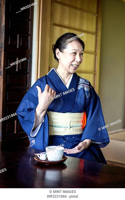 Smiling Japanese woman wearing blue kimono sitting on floor in traditional Japanese house