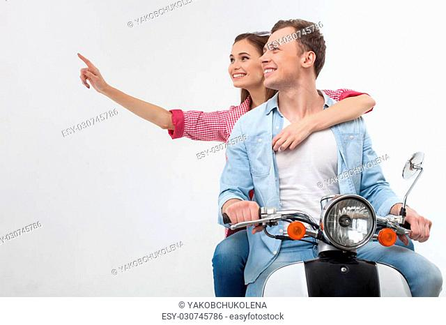 Look at that. Portrait of cute young loving couple driving the scooter in Spring. The woman is pointing finger sideways and smiling
