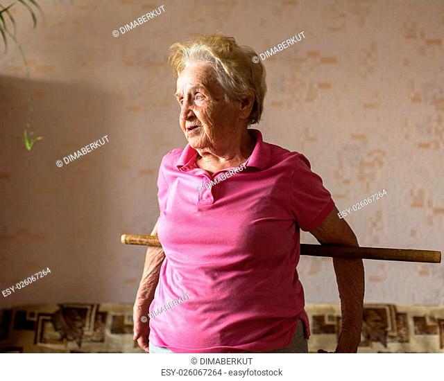 Elderly woman doing rehab exercises with a stick at his home