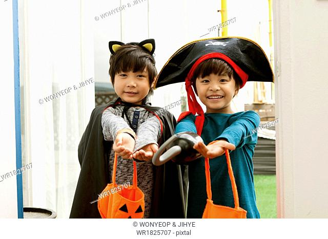two boys in a Halloween costumes getting candy