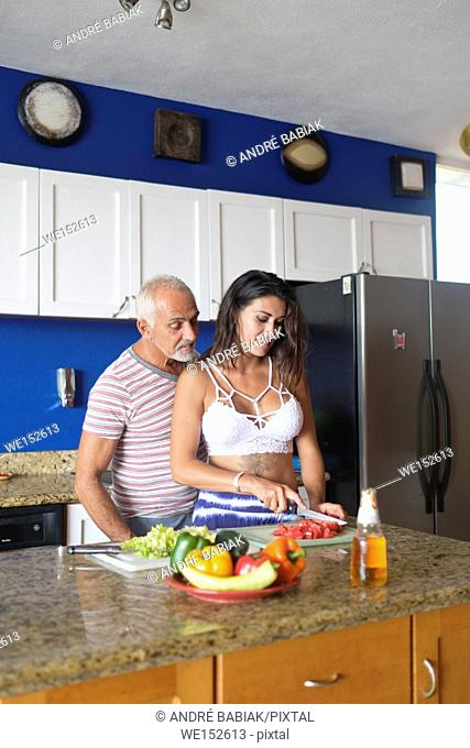 Older man and young woman enjoying cutting vegetables in their kitchen