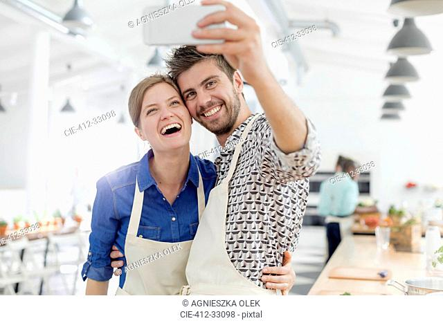 Enthusiastic couple taking selfie with camera phone in cooking class kitchen