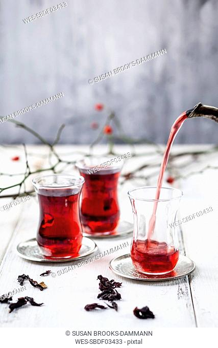 Pouring hollyhock tea in tea glass