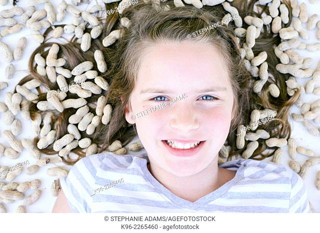 young girl looking at camera surrounded by peanuts