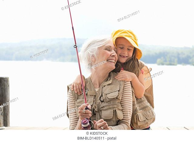 Caucasian grandmother and granddaughter fishing at lake