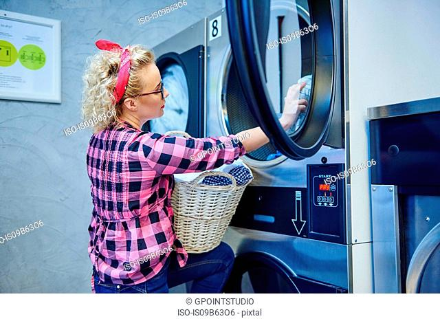 Woman removing laundry from tumble dryer in laundrette