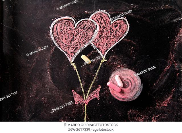 Done graphical representation with chalk on blackboard symbol of love, the heart
